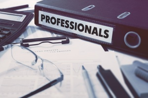 Professionals - Office Folder on Background of Working Table with Stationery, Glasses, Reports. Business Concept on Blurred Background. Toned Image.