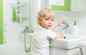 boy washing hands in bathroom